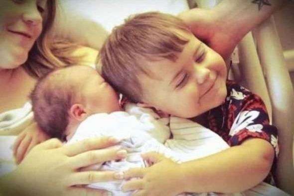 мальчик обнимает новорожденного